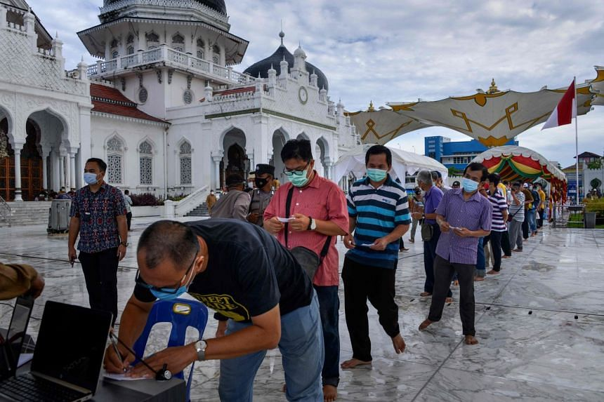 People wait in a queue for Covid-19 vaccine shots in front of the Baiturrahman grand mosque in Indonesia's Banda Aceh on March 30, 2021.
