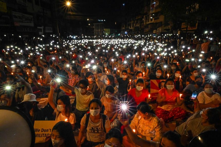 Protesters taking part in a candlelit vigil in Yangon on March 13, 2021.