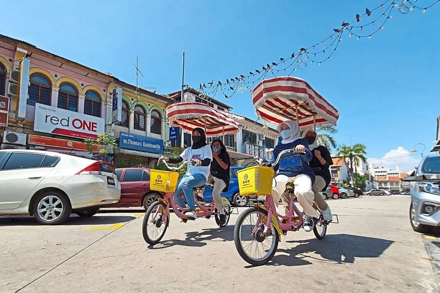 Local residents taking in the sights of George Town on rented bicycles.
