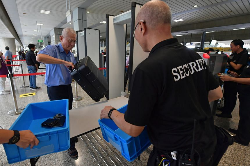 In a photo taken on April 4, 2019, a commuter has his belongings checked and scanned by X-ray machines before going through the metal detector at Jurong East MRT Station.