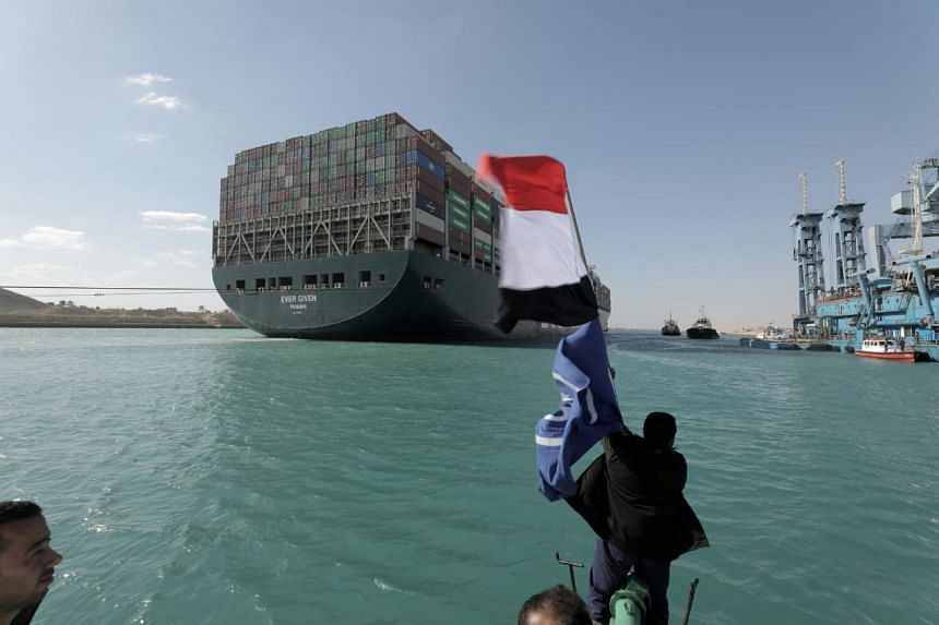 A man waves an Egyptian flag as the Ever Given is seen after it was fully floated in the Suez Canal, March 29, 2021.
