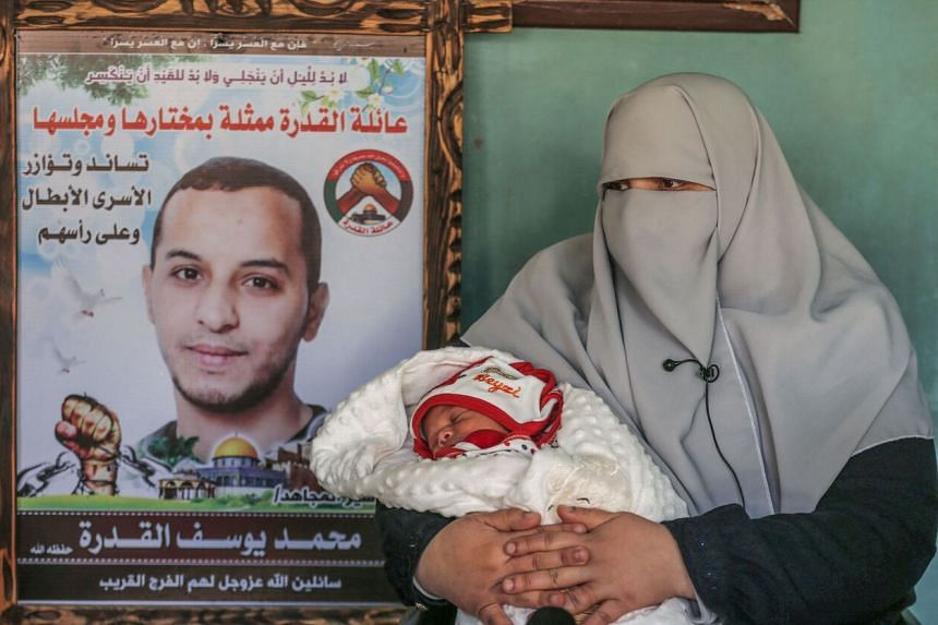 Ms Iman al-Qudra holds her newborn baby,  who was conceived with smuggled sperm from her husband who is jailed in Israel.