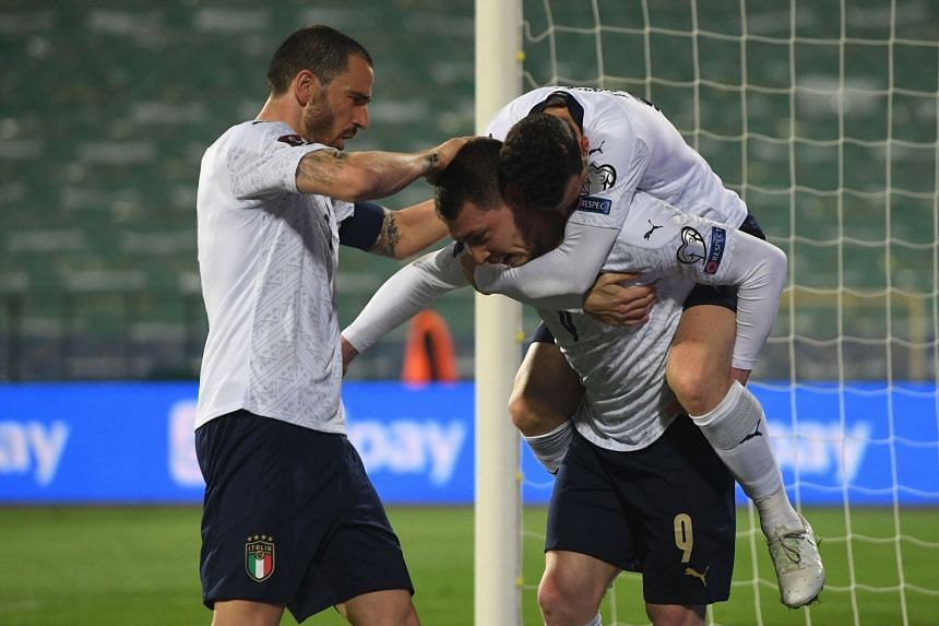 Italy's Andrea Belotti (centre) celebrates with team-mate Leonardo Bonucci (left) after scoring a penalty goal during the team's World Cup qualifier against Bulgaria on March 28, 2021.