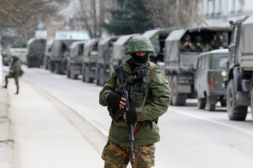 A 2014 photo shows armed servicemen waiting in Russian army vehicles outside a Ukranian border guard post in the Crimean town of Balaclava.