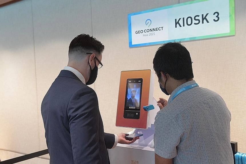 Above: A guest at Geo Connect Asia 2021, held last month, using a self-service kiosk with a facial recognition system that registers attendees without requiring face-to-face interaction. ST PHOTO: ALPHONSUS CHERN Left: The Professional Convention Man