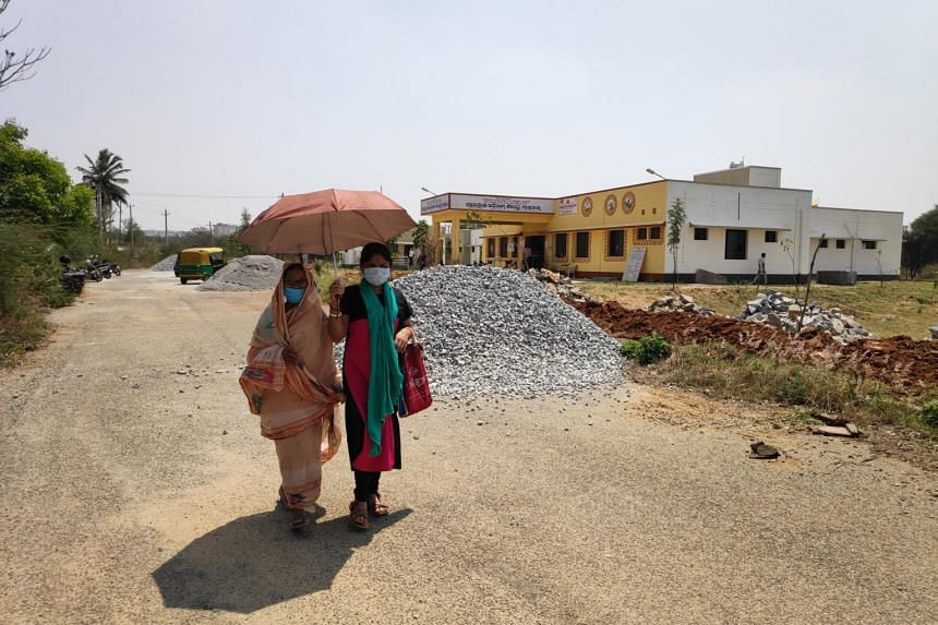 A woman taking her mother home from the Guddahatti health centre in Karnataka, India, after the older woman's first vaccine dose.