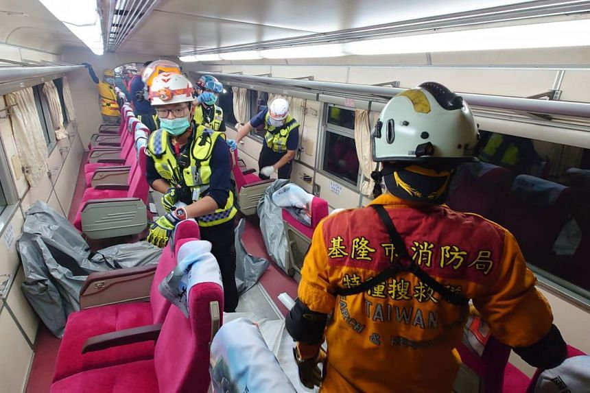 Rescuers moving body bags of victims on the train.