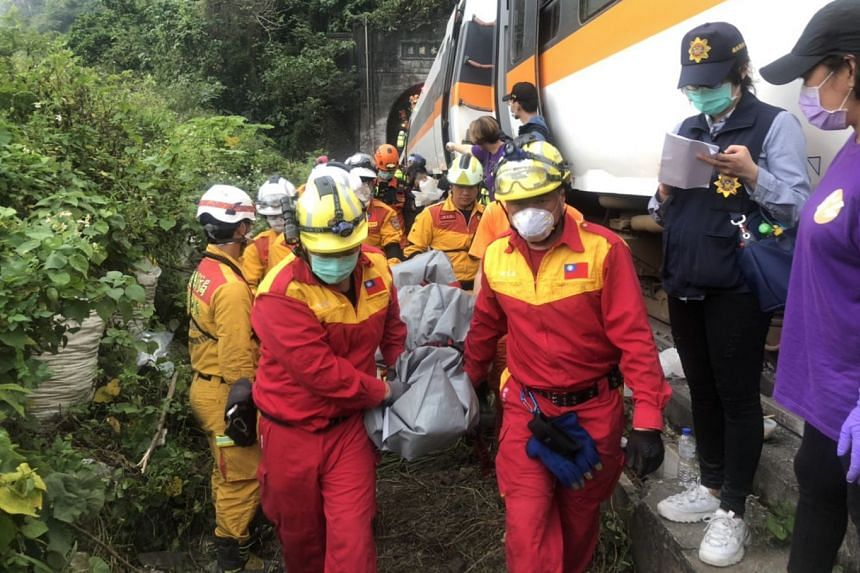 A Keelung City Fire Department photo shows rescuers removing the body bags of victims from the site of the crash.
