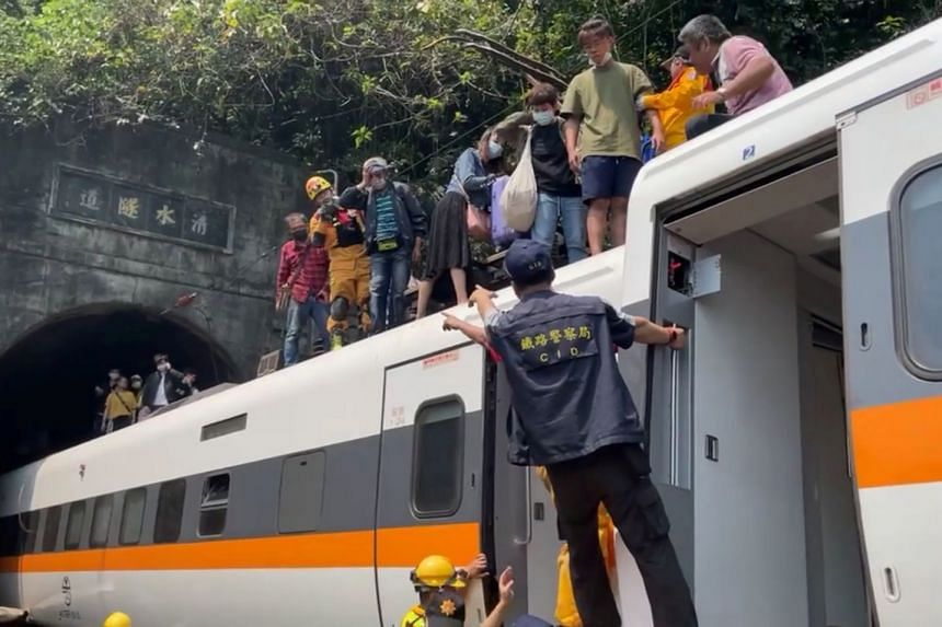 Rescuers help stranded passengers down from the roof of the train which derailed in a tunnel north of Hualien, Taiwan.