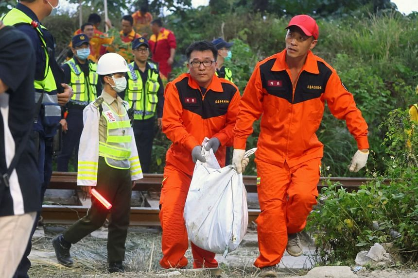 Rescuers carry a body at the site of the train derailment in a tunnel north of Hualien, Taiwan.