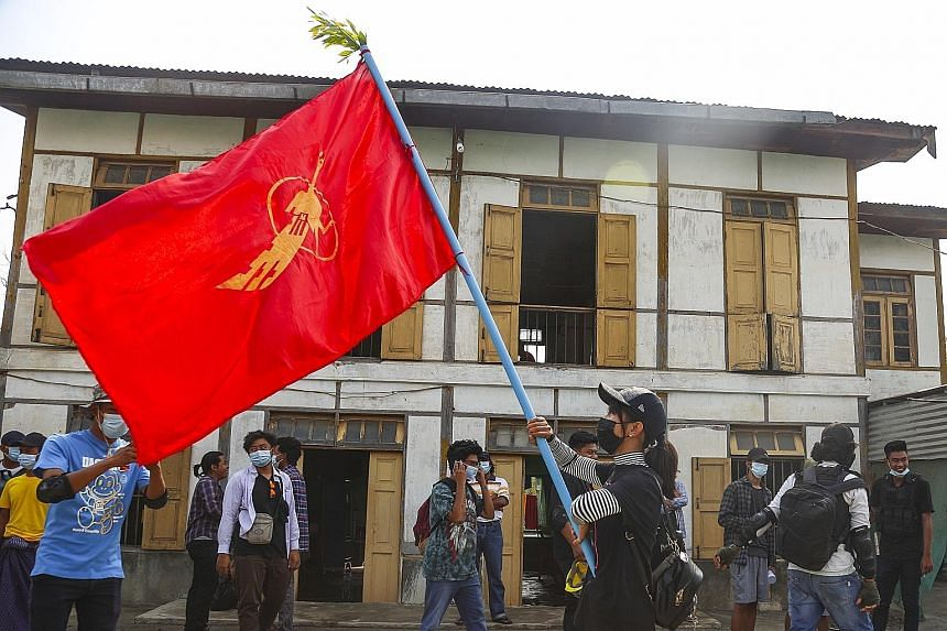 A demonstrator waving a student union flag during a protest yesterday in Mandalay against the military coup in Myanmar. The extent of the Internet shutdown was not immediately clear, with pictures of marches and a funeral of a slain protester still b