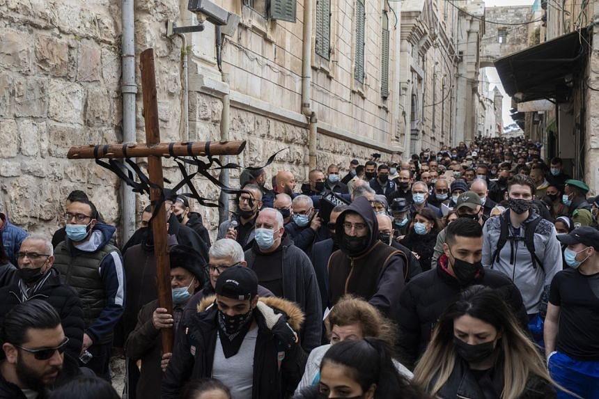 Christian worshippers walk with a large cross during a Good Friday procession in Jerusalem, on April 2, 2021.