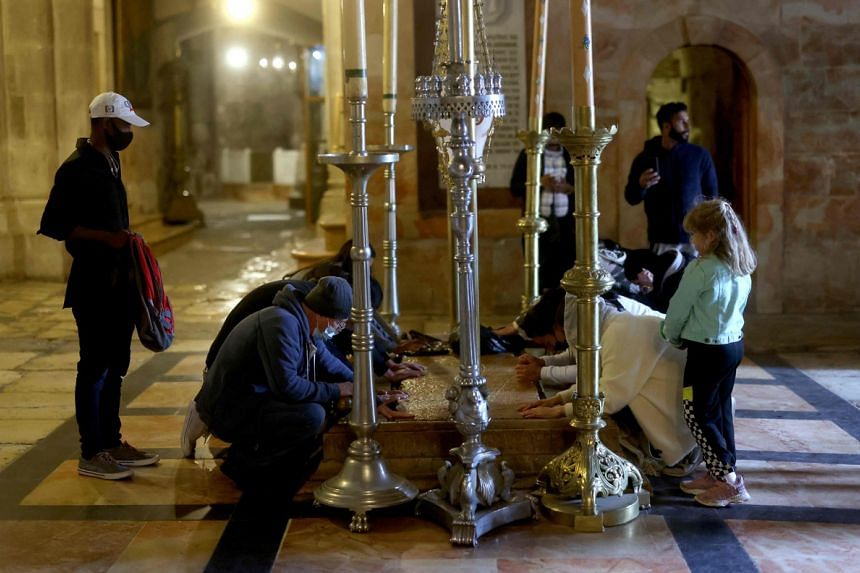 Christian worshippers pray over the stone of Anointing, believed to be the place where Jesus Christ's body was laid after crucifixion, at the Church of the Holy Sepulchre in Jerusalem's Old City, on April 2, 2021.