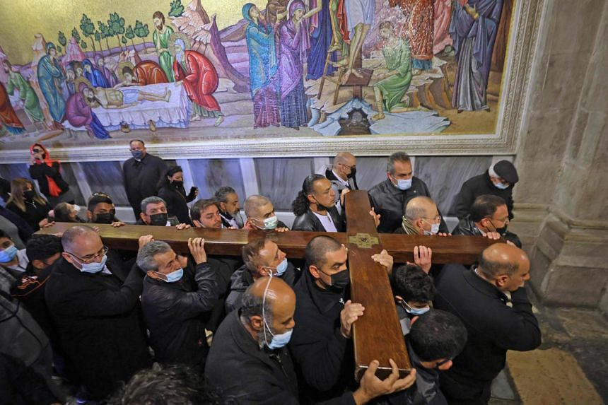 Worshippers carrying a wooden cross arrive at the Church of the Holy Sepulchre, during a Good Friday procession in Jerusalem's Old City, on April 2, 2021.