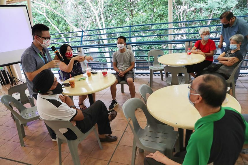 IHH Healthcare Singapore's Noel Yeo (standing, left) and Pasir Ris-Punggol GRC MP Yeo Wan Ling (in red mask) fielding questions at a foodcourt on March 21, 2021.
