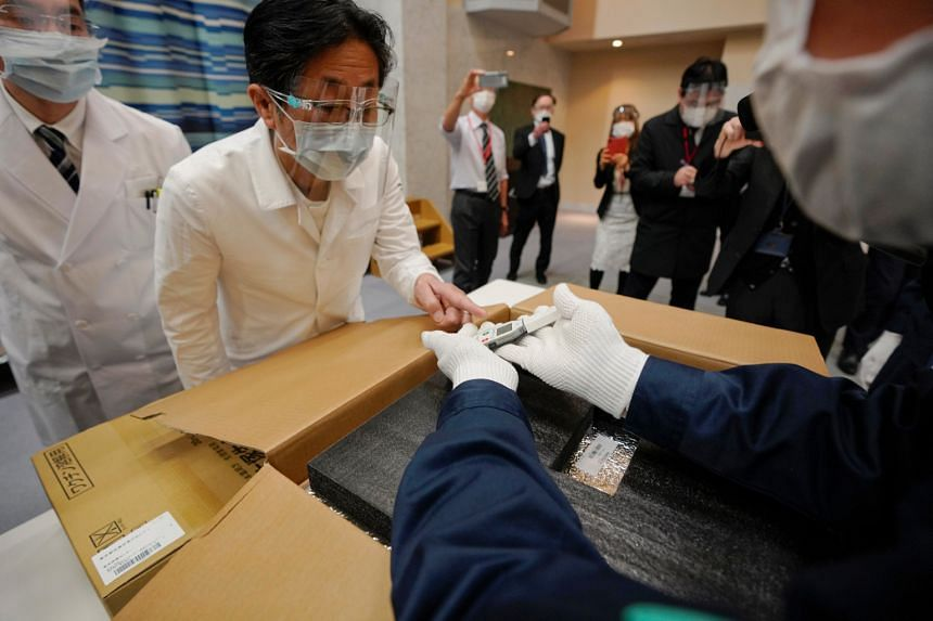 A Tokyo hospital staff member checks the condition of Pfizer's Covid-19 vaccine with delivery staff at a hospital in Tokyo, on Feb 16, 2021.