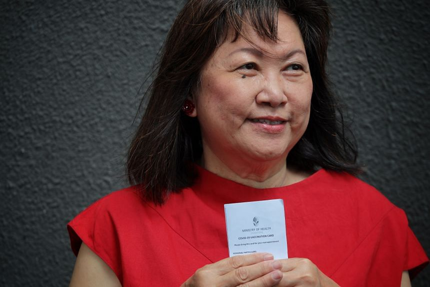 Retiree Mah Koon Sin poses for a photo with her vaccination card on March 23, 2021.