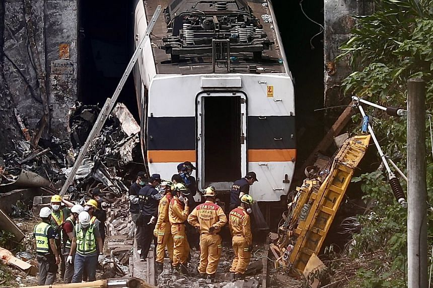 Investigators inspect the wreckage of a yellow truck that hit the train which derailed in a tunnel north of Hualien, Taiwan, on April 3, 2021.