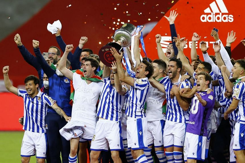 Real Sociedad players celebrate winning the Copa del Rey with the trophy.