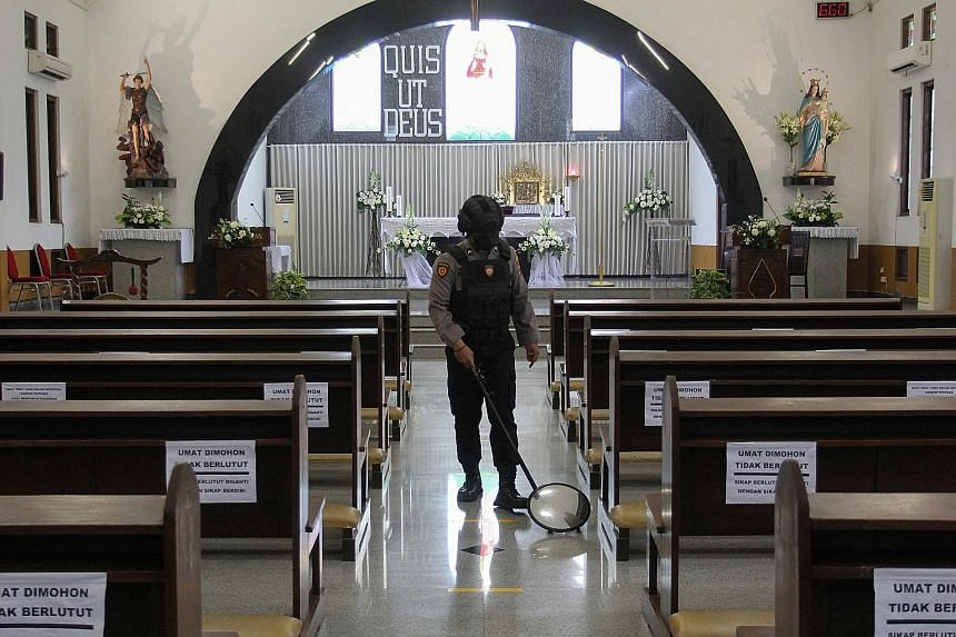 A police officer inspecting church pews in Surabaya last Thursday. Security forces were on heightened alert following the terror attack in Makassar on Palm Sunday. PHOTO: REUTERS