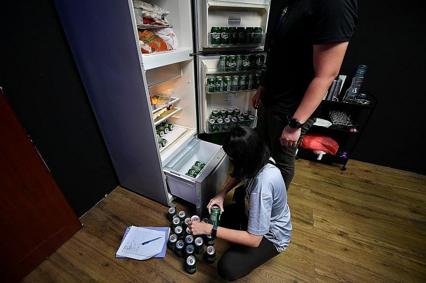 Above: A police officer counting cans of beer yesterday in a unit suspected of housing an unlicensed public entertainment outlet. Left: People being investigated during a raid. Besides the eight arrested, 34 men and 11 women will be probed for suspec