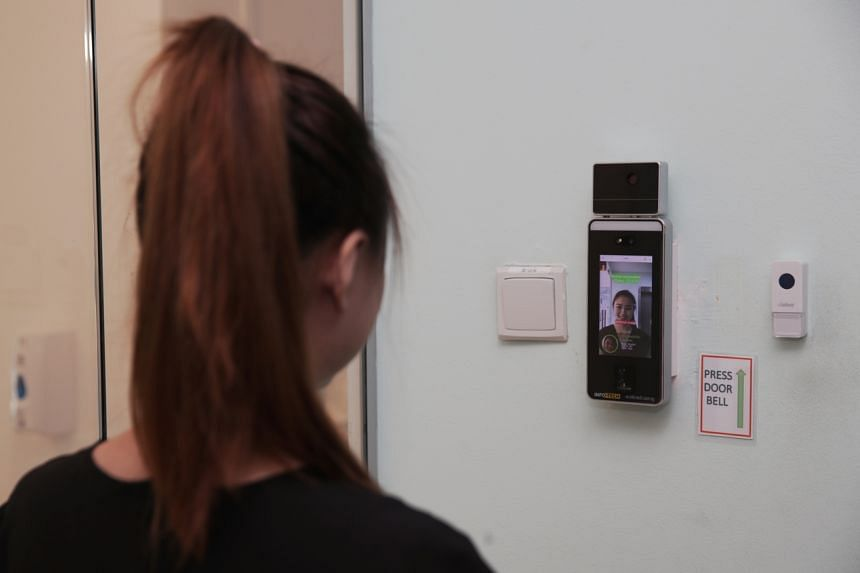 A facial-recognition temperature scanner in use.