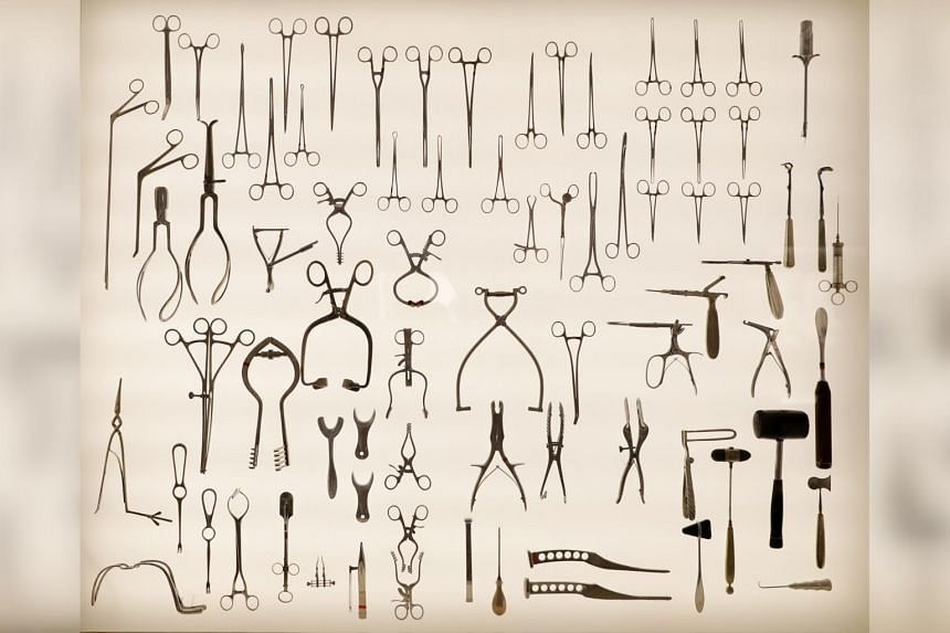 The collection includes obstetric delivery forceps used by doctors, self-retaining retractors, bone-nibbler clamps, mallots, curettes, bone hooks, osteotome, rongeurs, and a little axe saw used to cut parts of the skull. Some of these surgical instru