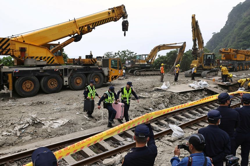Police officers move passengers' belongings from the site of a deadly train derailment at Hualien, Taiwan, on April 3, 2021.