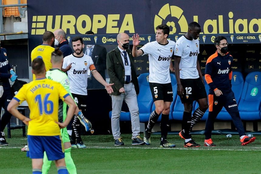 Valencia's Mouctar Diakhaby (right) leaves the pitch with his teammates after allegedly receiving a racist comment by Cadiz's Juan Cala (left) during their match on April 4, 2021.