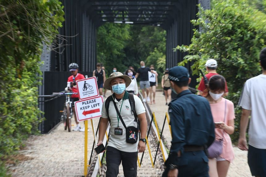 An enforcement officer at the Upper Bukit Timah Truss Bridge of the Rail Corridor on April 4, 2021. Officers from NParks and Aetos stepped up patrols over the long Easter weekend to manage crowds along the trail.