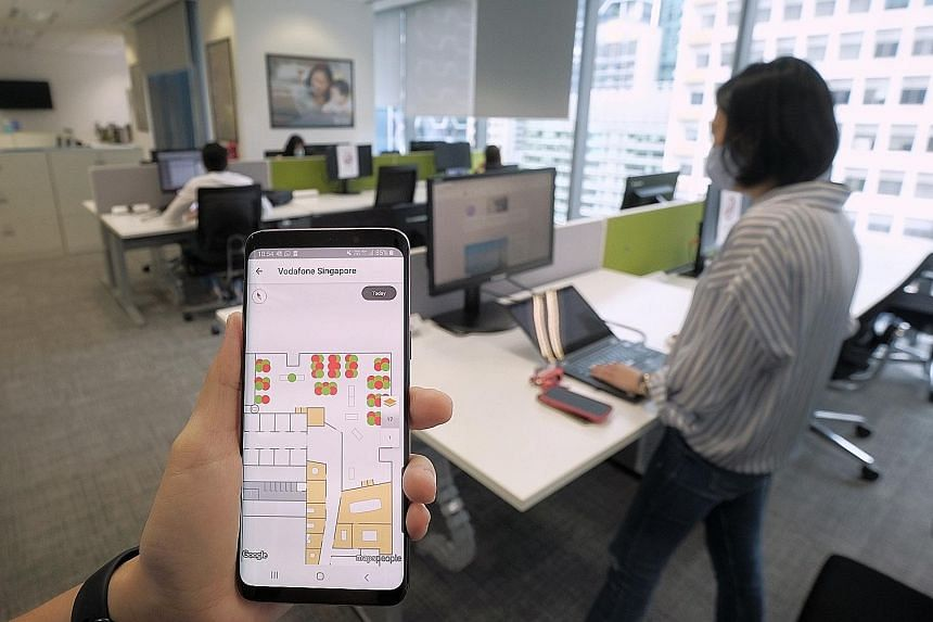 A smartphone app being used by a Vodafone staff member to check and book slots for workstations at the firm's office in Marina Bay. With fewer workers in the office, companies may choose to downsize and save on rent. Some are also redesigning the wor