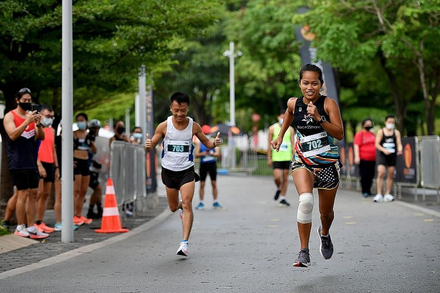 Shiela Cory Sacayanan and Tan Kok Soon (No. 703) competing at the Leaderboard 5km Finale Run at the Singapore Sports Hub yesterday. They finished 15th and 20th in the women's and men's race respectively.