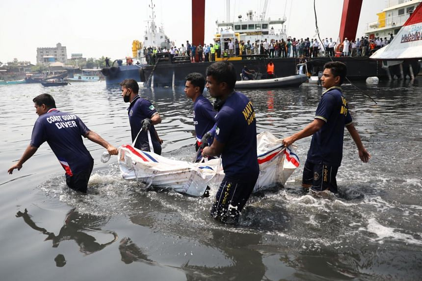 Rescue workers carry a body recovered from the ferry that sank in the  Shitalakshya River in Narayanganj, Bangladesh, on April 5, 2021.