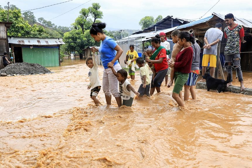 People wade through flood water at a residential area in Dili, East Timor, on April 4, 2021.