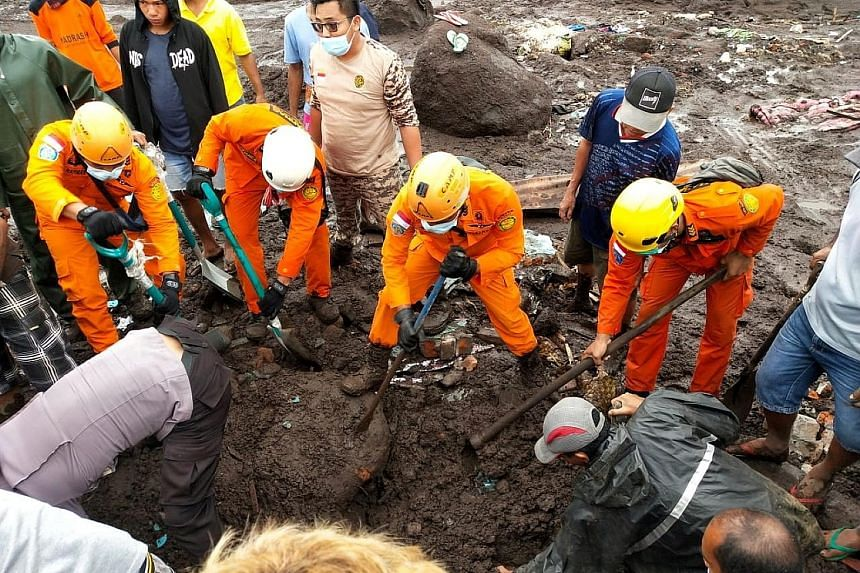 Rescue workers searching for a body in an area affected by flash floods after heavy rain in East Flores in Indonesia's East Nusa Tenggara province yesterday. At least 70 people in the country have died in flash floods and landslides, while over 30,00