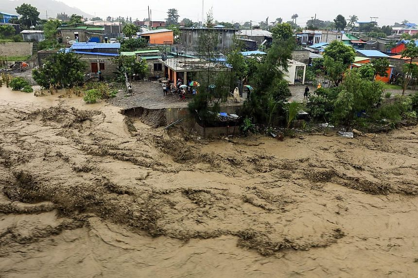 People keeping to higher ground as a river swelled due to flooding in Dili, Timor-Leste, on Sunday. At least 27 people in the country were killed by landslides, flash floods, as well as a falling tree, while 7,000 were displaced.