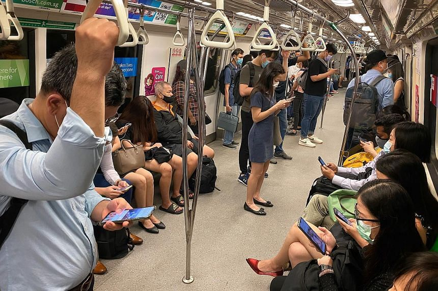Commuters on a train heading towards the CBD at Outram Park MRT station yesterday at 8.30am. Although it was the first day of eased regulations giving companies more leeway to shift from working from home, most commuters The Straits Times spoke to di