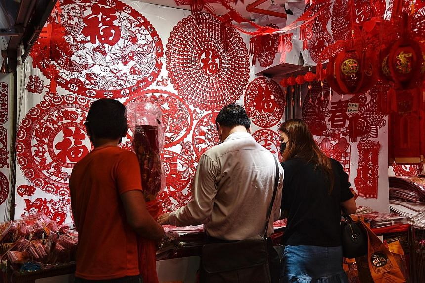 People shopping for decorations in Chinatown, ahead of Chinese New Year in February. The Department of Statistics said the improvement in retail sales in February was mainly associated with CNY celebrations that month, whereas last year, the festive