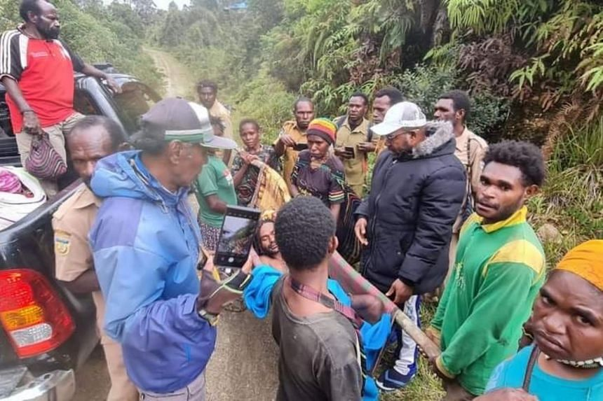 Janius Bagau carried by his two brothers, Soni (black T-shirt) and Yustinus (in green and yellow top) to a local health clinic on Feb 15, 2021.