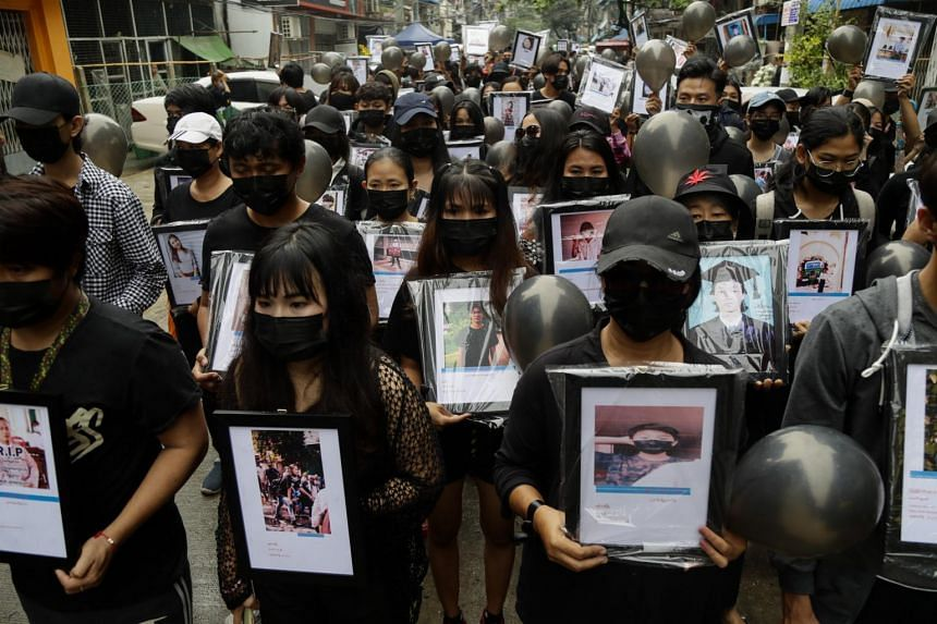 Demonstrators hold black balloons and pictures of victims who were shot dead by armed troops in Yangon on April 5, 2021.