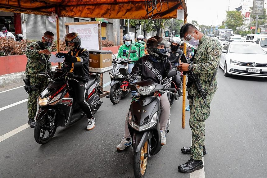 Police officers in the Philippines on Sunday manning a checkpoint between Quezon City and Manila, which is under lockdown. Police officers outside closed shops in Athens in February, during a lockdown. Aware of the toll of strict shutdowns on people
