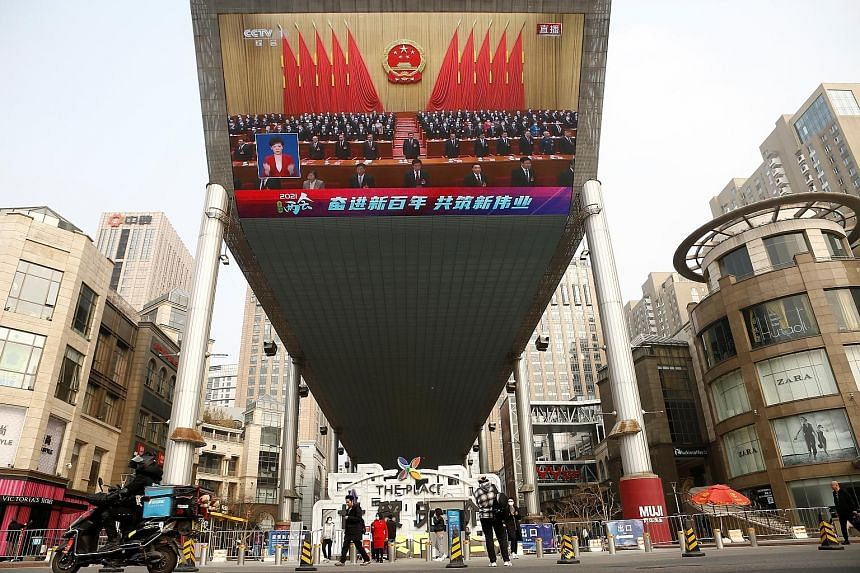 A giant screen showing Chinese President Xi Jinping at the National People's Congress in Beijing on March 11. Panellists at a forum in Singapore on Monday agreed that China would overtake the US as the world's largest economy, but not because of Chin