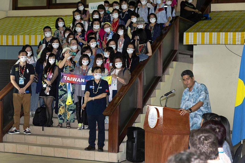 In a photo taken on April 1, 2021, Palau President Surangel Whipps (right) greets tourists from Taiwan during their arrival in Koror.