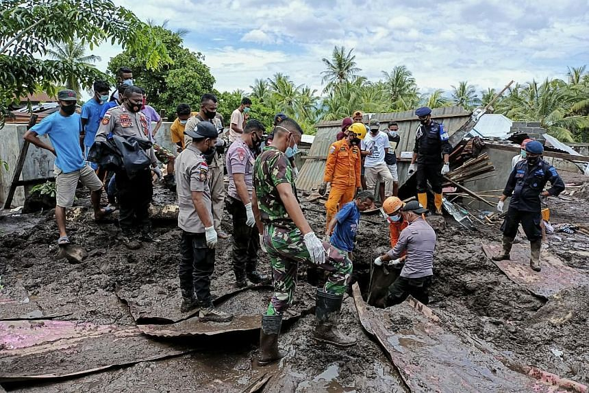 Rescuers search for victims under the debris after a flash flood hit a village in Adonara, East Flores, Indonesia, on April 6, 2021.