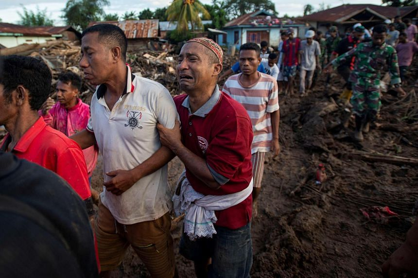 A man cries over his relative who was found dead following flash floods in East flores, Indonesia, on April 6, 2021.