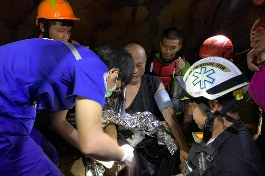 Thai rescue workers taking the blood pressure of the monk after he was found in the cave, on April 7, 2021.