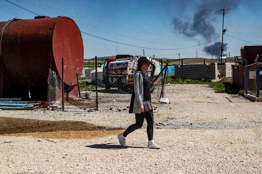 Frenchwoman Emilie Konig walks in Camp Al-Roj in northeastern Syria, on March 28, 2021.