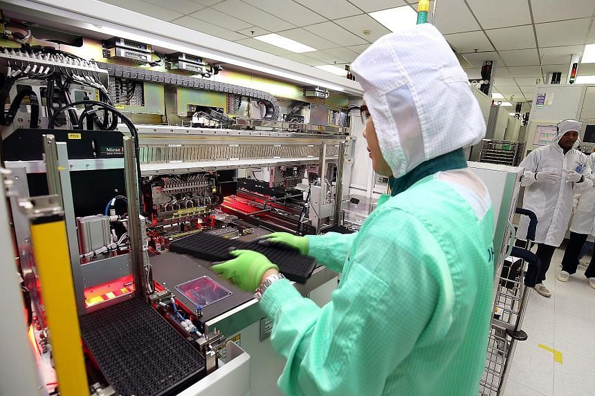 A 2017 file photo of a worker at semiconductor giant Infineon placing integrated circuit packages onto boards.