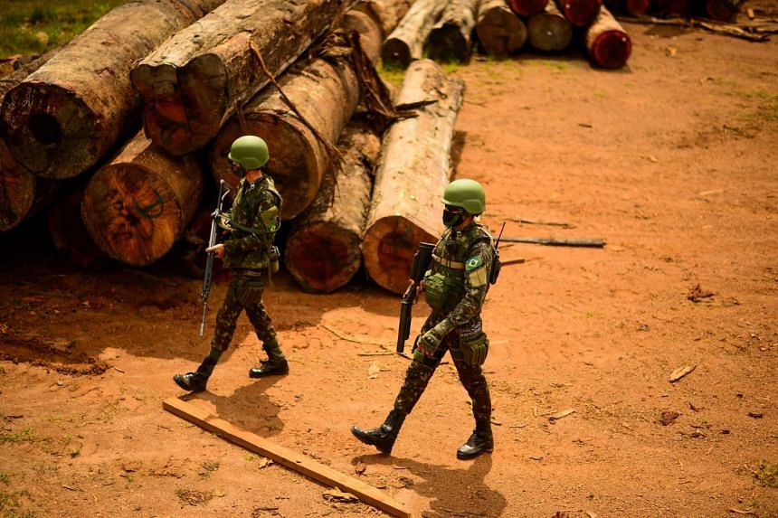 A May 2020 photo shows Brazilian army soldiers walking next to piles of lumber cut illegally from the Amazon rainforest during an operation in Porto Velho, Rondonia state.