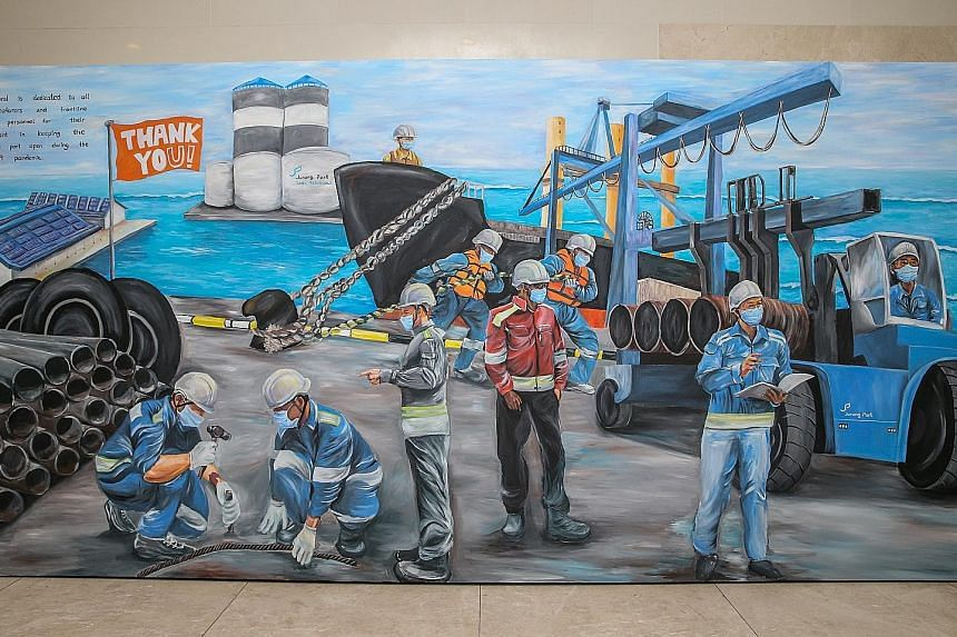 Above: (From right) Mr Jaxton Su, 33, Mr Klein Aw, 21, and Ms Elizabeth Goh, 26, touching up the mural at PSA's Pasir Panjang Terminal yesterday. The Jurong Port mural (top) highlights the vital role of maritime personnel in maintaining international